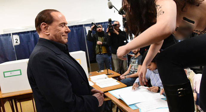 Topless Femen protester confronts Berlusconi at polling station